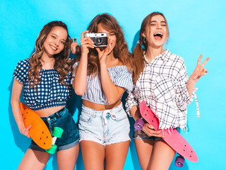 Three sexy beautiful stylish smiling girls with colorful penny skateboards.Women in summer hipster checkered shirt clothes posing near blue wall. Models taking pictures on retro camera