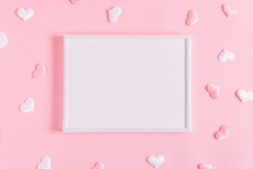 Valentine's Day composition. Photo frame and hearts on pastel pink background. Wedding. Birthday. Happy woman's day. Mothers Day. Flat lay, top view, copy space