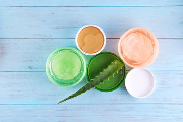 gel serum of snail collagen and Fresh Aloe Vera Gel in jar on blue wooden background. Snail gel is natural remedy for sunburn relief and cure many things