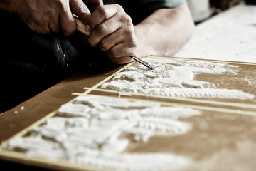 craftsman hands using a gouge to make an intricate carving