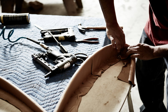 craftsman hands working on leather upholstery