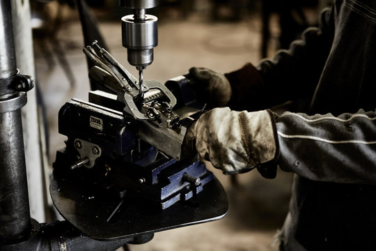 worker wearing heavy gloves using drill press