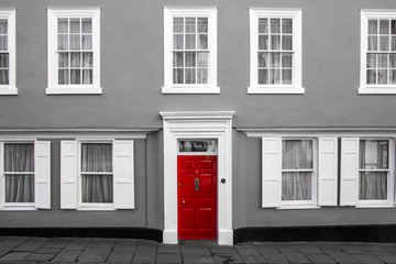 A facade of a traditional village house in Great Britain. Its red door are isolated in a black and white picture.