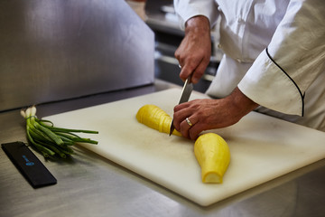 Chef slicing yellow squash on white cutting board