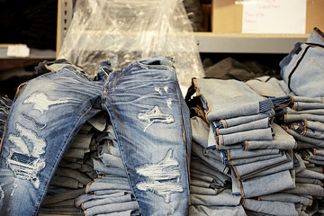 Distressed jeans on pile of denim jeans
