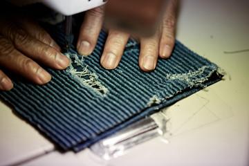 Romans hands sewing denim on sewing machine