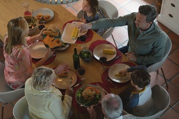 Multi-generation family having food on dining table