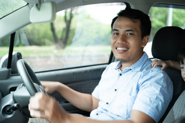 young asian driver smile to the camera when drive a car