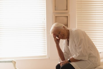 Depressed senior woman sitting in bedroom