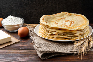 Stack of homemade pancakes blini on wooden background. Russian Maslenitsa, Shrove tide, pancake week, carnival, pancake day.