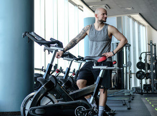 Athletic man with a tattoo on his hand standing next to a exercise bike in the modern fitness club