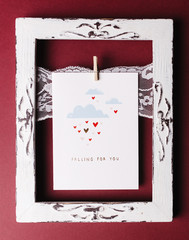 Valentines day card in the white frame on the red background photographed from above