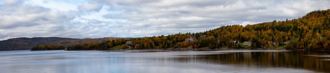 Beautiful panoramic landscape view of residential homes by the lake during a cloudy day. Taken at Georges Lake, Newfoundland, Canada.