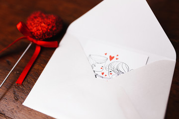 Envelope with valentines day card and the figure of heart on the wooden background