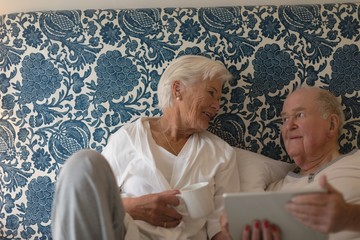 Senior couple using digital tablet in bedroom