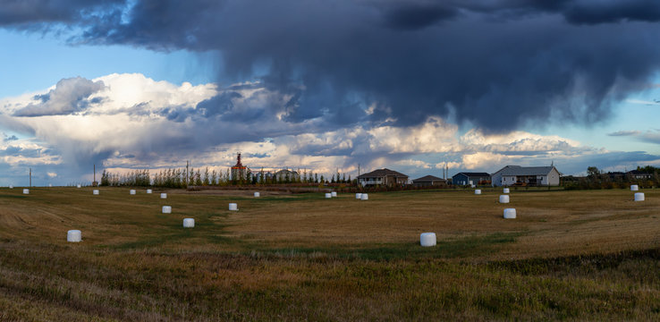 Panoramic view of farm fields with Hay Bales during a cloudy and stormy evening. Taken West of Winnipeg, Manitoba, Canada.