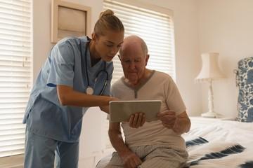 Female doctor and senior man using digital tablet