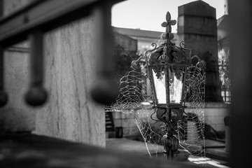 A detail Picture of an old lantern on an old cemetery. There are spider webs on it and it looks gloomy.