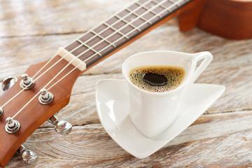 cup of coffee and ukulele on rustic wood.