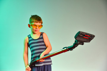 Boy in yellow goggles holding a vacuum cleaner handle