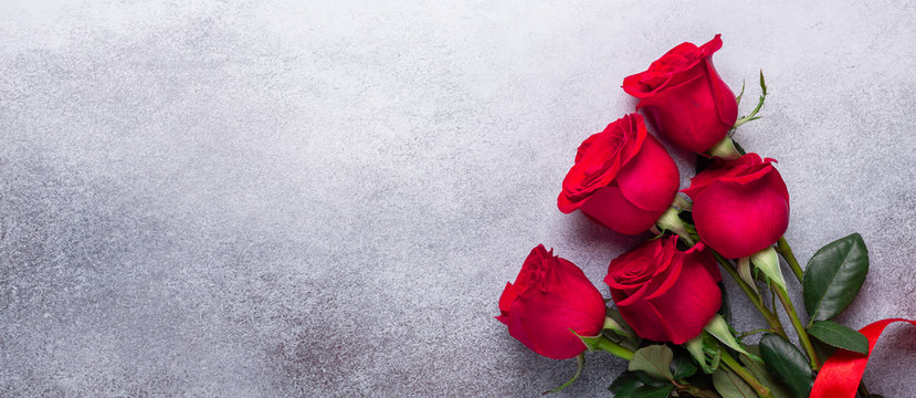 Red rose flowers bouquet on stone background Valentine's day greeting card Copy space Flat lay Horizontal banner