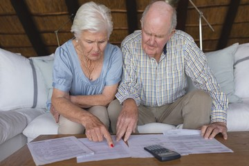 Senior couple discussing over medical bills in living room