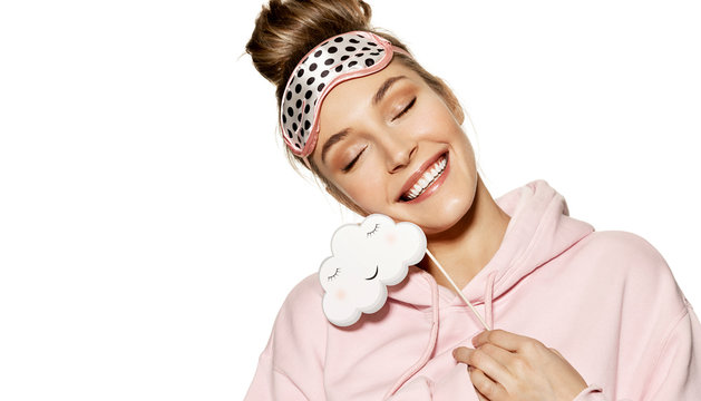 Portrait of happily smiling model posing in cute sleeping mask and holding cloud sign with copy space for text. Lovely girl in pink outfit on white background