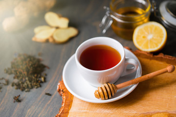 Cup of tea with lemon, ginger, honey and honey stick on wooden rustic table .