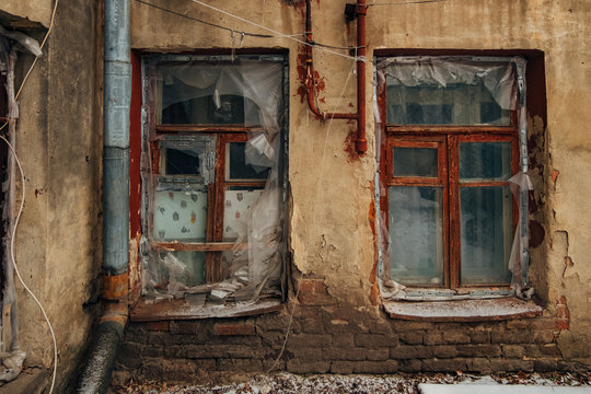 Shabby grungy cracked wall, broken windows, covered buy cloth and polyethylene film, winter, poverty concept