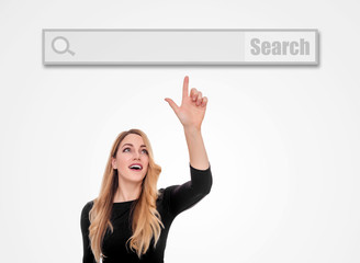 An attractive young woman points the finger at the blank line of a virtual search Internet browser.