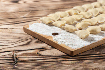 Raw dumplings on wooden cutting board, is ready to boil. Also known as Vareniks. Ukrainian traditional cuisine