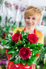 Florist lady showing beautiful bouquet  of roses, perfect present for Valentine's day