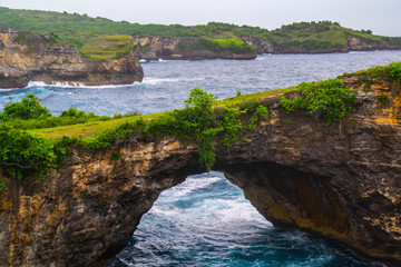 Beautiful view of unique Angels Billabong at Nusa Penida Island, Bali, Indonesia. Turquoise sea water, green grass and vacation mood. Must visit place in Bali.