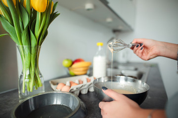 Girl cooking pancakes in the kitchen, home with flowers, eggs, fruits on the table.