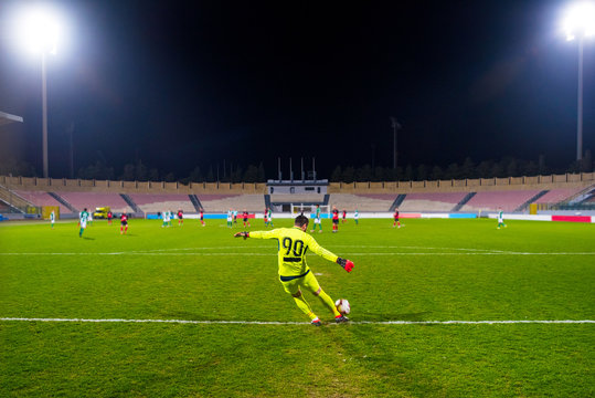 Goalkeeper kicking the ball at the stadium, in the spotlight
