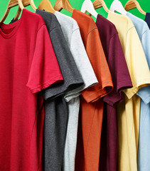 Colorful T-shirts on a green background