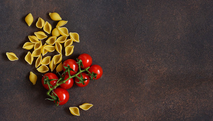 Pasta and tomatoes on a concrete background. Italian food background. Ingredient for cooking.