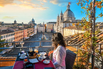 A woman enjoys the view of Rome, Italy and the Piazza Navona as she finishes her continental breakfast from a rooftop terrace of a luxury hotel early on a summer morning.