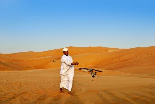 Falconer in the desert luxury hotel Anantara Qasr Al Sarab, in the middle of high sand dunes, in the Empty Quarter called sand desert Rub Al Khali, Emirate of Abu Dhabi, United Arab Emirates, Asia