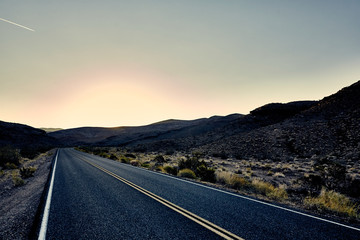 paved desert road leading into horizon at sunset
