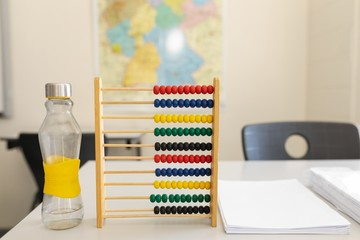 Water bottle, abacus and bunch of paper on the desk in school