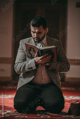 Muslim man praying and reading Quran