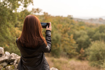 A young red-haired woman takes pictures with her mobile phone in a forest