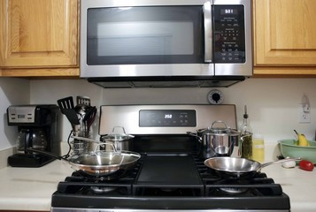 Modern stainless steel gas stove oven with stainless steel cookware.