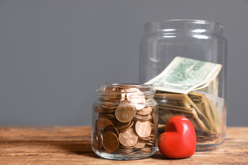 Red heart and donation jars with money on wooden table against grey background. Space for text