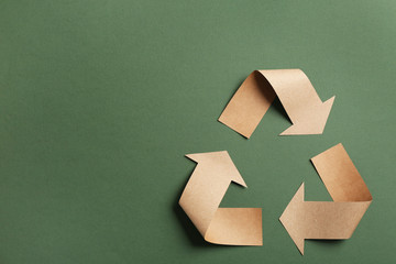 Recycling symbol cut out of kraft paper on green background, top view. Space for text Wall mural