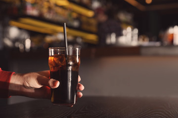 Man holding glass of refreshing cola at table indoors, closeup. Space for text