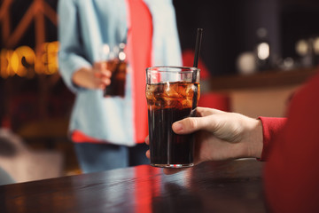 Man holding glass of cola at table in bar, closeup. Space for text