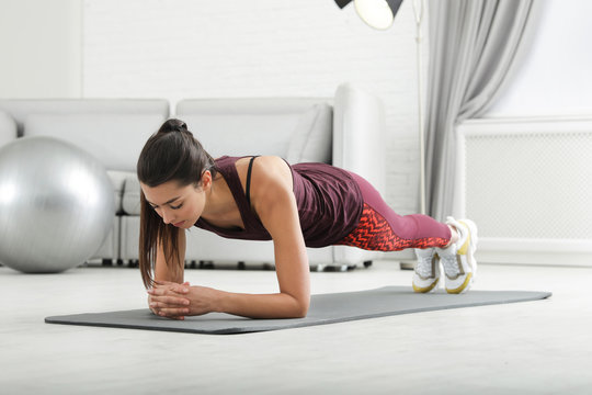 Young woman in fitness clothes doing exercise at home