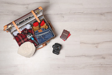 Suitcase with clothes, passports and camera on wooden background, top view with space for text. Winter vacation